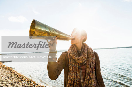 Young woman using megaphone by lake Stock Photo - Premium Royalty-Free, Image code: 649-07521116
