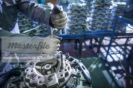 Close up of engineer assembling industrial clutch on production line Stock Photo - Premium Royalty-Free, Image code: 649-07521189
