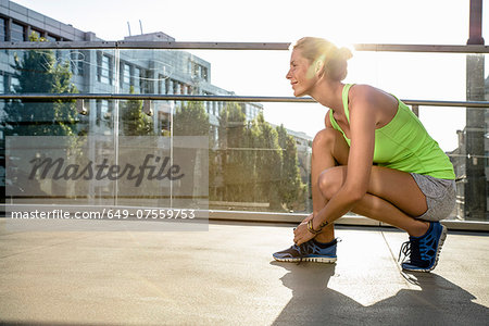 Young female runner tying shoelace on city footbridge Stock Photo - Premium Royalty-Free, Image code: 649-07559753