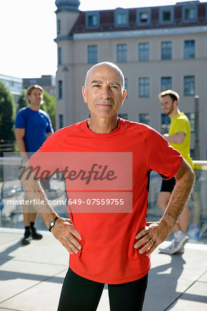 Mature male trainer and class taking a break on city rooftop Stock Photo - Premium Royalty-Free, Image code: 649-07559755