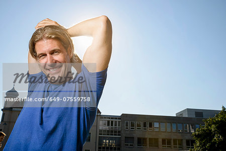 Mid adult man stretching during training on city rooftop Stock Photo - Premium Royalty-Free, Image code: 649-07559758