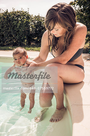 Mother and baby daughter paddling in swimming pool Stock Photo - Premium Royalty-Free, Image code: 649-07559772