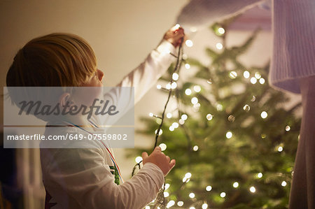 Young boy putting up christmas tree lights Stock Photo - Premium Royalty-Free, Image code: 649-07559802
