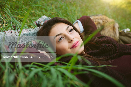 Young woman lying on blanket on grass Stock Photo - Premium Royalty-Free, Image code: 649-07559826