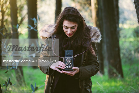 Young woman with camera in the woods Stock Photo - Premium Royalty-Free, Image code: 649-07559829