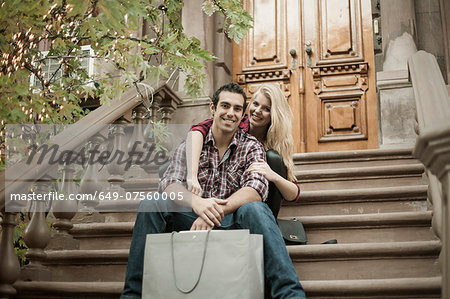 Young couple sitting on traditional city apartment steps Stock Photo - Premium Royalty-Free, Image code: 649-07560005