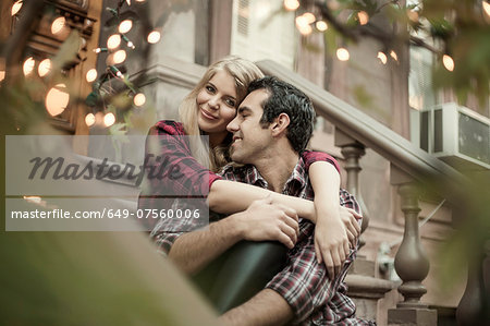 Happy couple sitting on traditional city apartment steps Stock Photo - Premium Royalty-Free, Image code: 649-07560006