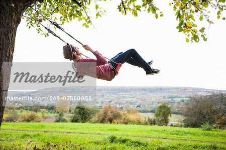 Man on swing Stock Photo - Premium Royalty-Free, Image code: 649-07560056