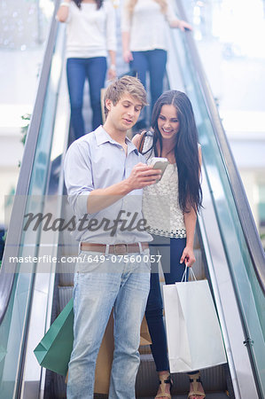 Young couple using cellular phone on escalator Stock Photo - Premium Royalty-Free, Image code: 649-07560057