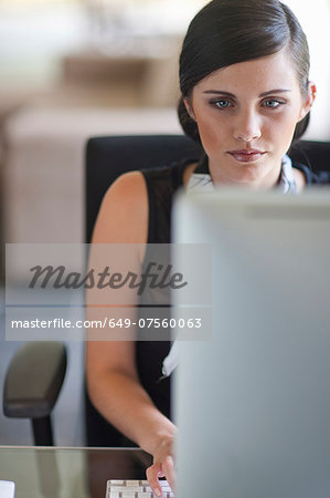 Young office worker using computer Stock Photo - Premium Royalty-Free, Image code: 649-07560063