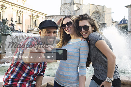 Tourist friends taking self portrait, Plaza de la Virgen, Valencia, Spain Stock Photo - Premium Royalty-Free, Image code: 649-07560087