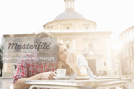 Young couple having coffee in sidewalk cafe, Plaza de la Virgen, Valencia, Spain Stock Photo - Premium Royalty-Free, Image code: 649-07560108