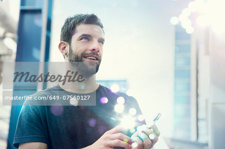 Mid adult man looking up at lights coming from smartphone Stock Photo - Premium Royalty-Free, Image code: 649-07560127