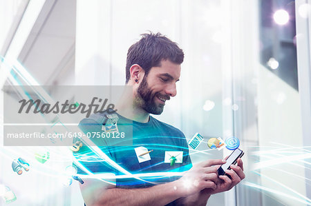Mid adult man with apps and lights coming from smartphone Stock Photo - Premium Royalty-Free, Image code: 649-07560128
