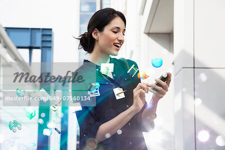 Young businesswoman holding smartphone with apps and icons coming out of it Stock Photo - Premium Royalty-Free, Image code: 649-07560134