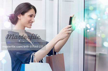 Young businesswoman looking at smartphone with lights coming out of it Stock Photo - Premium Royalty-Free, Image code: 649-07560137