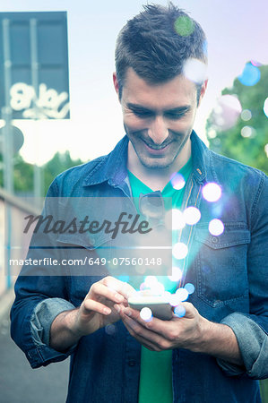 Young man texting on smartphone with glowing lights coming out of it Stock Photo - Premium Royalty-Free, Image code: 649-07560148