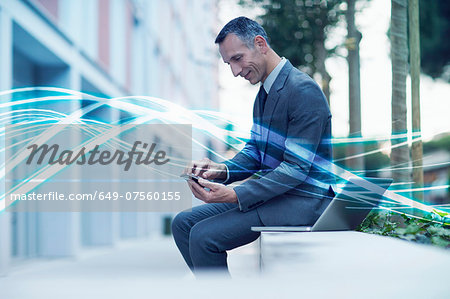 Waves of blue light and businessman texting on smartphone Stock Photo - Premium Royalty-Free, Image code: 649-07560155
