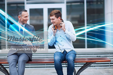 Businessman and young man watching digital tablet and waves of blue light Stock Photo - Premium Royalty-Free, Image code: 649-07560161