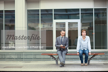 Businessman and young man sitting on train station bench Stock Photo - Premium Royalty-Free, Image code: 649-07560162