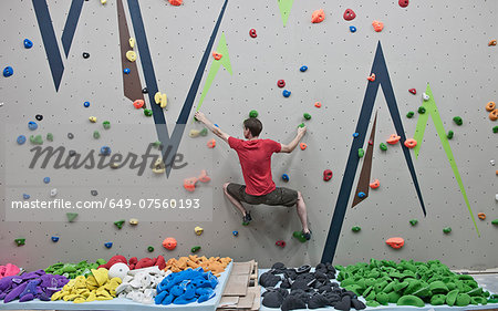 Route setter trying bouldering problem at indoor climbing wall Stock Photo - Premium Royalty-Free, Image code: 649-07560193
