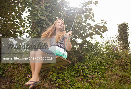 Girl daydreaming on garden swing Stock Photo - Premium Royalty-Free, Image code: 649-07560219