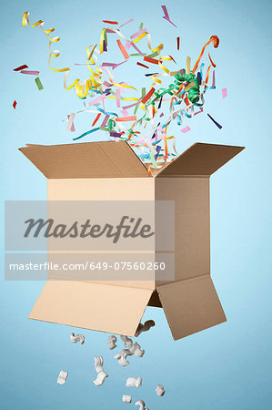 Studio shot of cardboard box with streamers exploding out Stock Photo - Premium Royalty-Free, Image code: 649-07560260