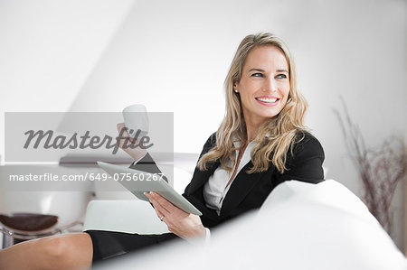 Mid adult businesswoman relaxing with digital tablet and a coffee Stock Photo - Premium Royalty-Free, Image code: 649-07560267