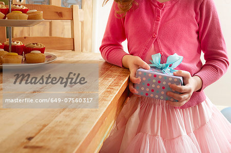 Girl holding birthday present, mid section Stock Photo - Premium Royalty-Free, Image code: 649-07560317