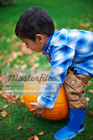 Male toddler in the garden picking up pumpkin Stock Photo - Premium Royalty-Free, Image code: 649-07560360