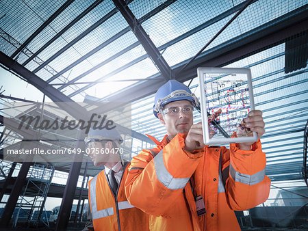 Builders working on plan details using digital tablet Stock Photo - Premium Royalty-Free, Image code: 649-07560470