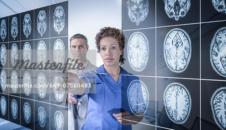 Doctor and nurse working with MRI brain scans seen through interactive display Stock Photo - Premium Royalty-Free, Image code: 649-07560483