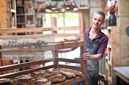 Portrait of young male baker with shelves of fresh bread Stock Photo - Premium Royalty-Free, Image code: 649-07585068