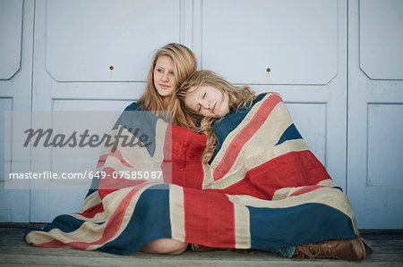 Portrait of sisters sitting on porch wrapped in union jack flag Stock Photo - Premium Royalty-Free, Image code: 649-07585087