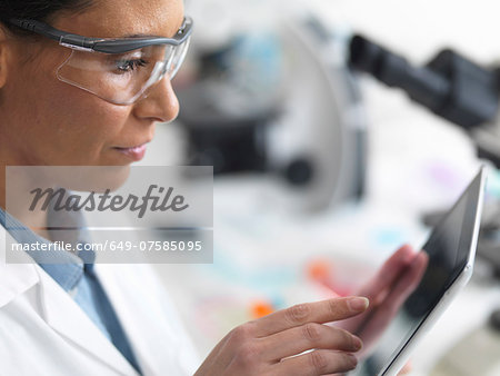 Female scientist viewing test results on a digital tablet in lab Stock Photo - Premium Royalty-Free, Image code: 649-07585095
