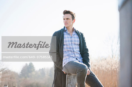 Mid adult man sitting on post on pier Stock Photo - Premium Royalty-Free, Image code: 649-07585141