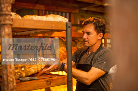 Mature man placing fresh bread on shelf Stock Photo - Premium Royalty-Free, Image code: 649-07585190