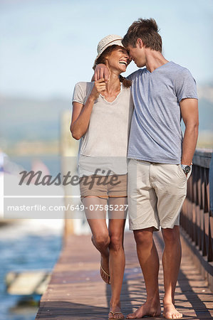 Young couple walking along jetty, arms around each other Stock Photo - Premium Royalty-Free, Image code: 649-07585227