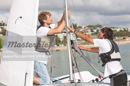 Two young men hauling up sail on boat Stock Photo - Premium Royalty-Free, Image code: 649-07585247