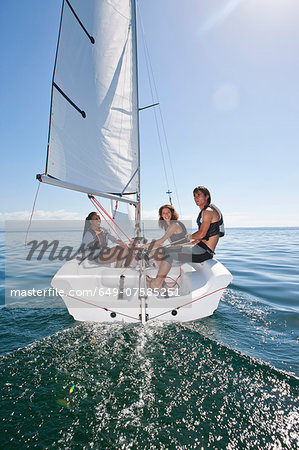 Three young friends relaxing on sailboat Stock Photo - Premium Royalty-Free, Image code: 649-07585251