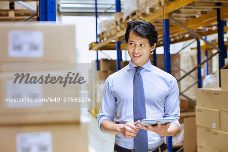 Mid adult male manager using digital tablet in distribution warehouse Stock Photo - Premium Royalty-Free, Image code: 649-07585276