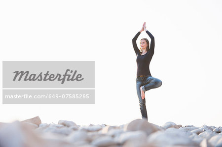 Young woman practicing yoga at coast Stock Photo - Premium Royalty-Free, Image code: 649-07585285