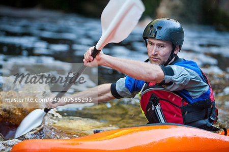 Close up of mid adult man kayaking on river rapids Stock Photo - Premium Royalty-Free, Image code: 649-07585293