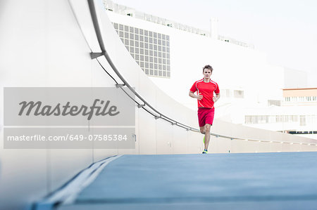 Mid adult male running in city car park Stock Photo - Premium Royalty-Free, Image code: 649-07585384