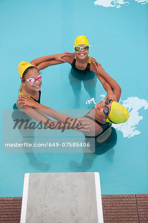 Portrait of three schoolgirl swimmers making circle Stock Photo - Premium Royalty-Free, Image code: 649-07585406