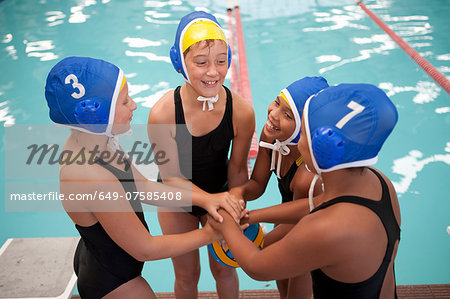 Four schoolgirl water polo players holding hands poolside Stock Photo - Premium Royalty-Free, Image code: 649-07585408
