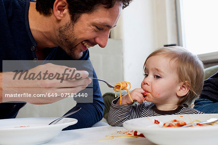 Father feeding one year old daughter spaghetti Stock Photo - Premium Royalty-Free, Image code: 649-07585440