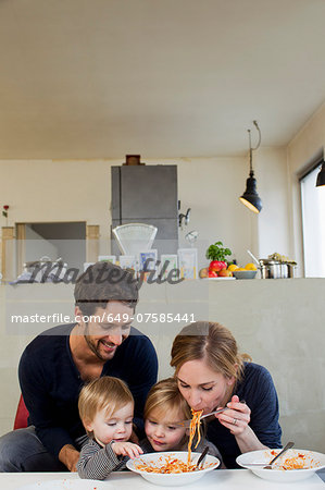 Family with two daughters eating spaghetti meal Stock Photo - Premium Royalty-Free, Image code: 649-07585441