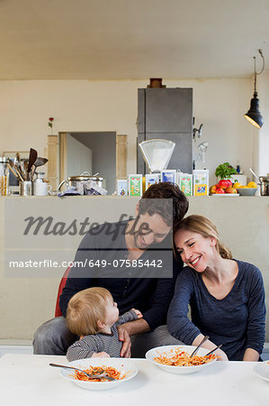 Family with baby girl eating spaghetti meal Stock Photo - Premium Royalty-Free, Image code: 649-07585442