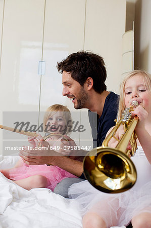 Father and two young daughters playing music Stock Photo - Premium Royalty-Free, Image code: 649-07585447